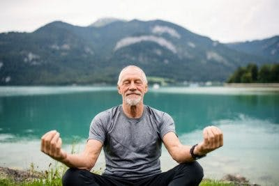 senior man meditating near lake, with mountain in the background