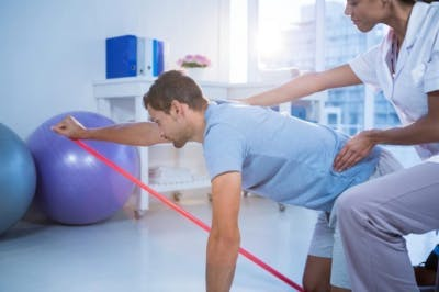 therapist helping hemiplegia patient exercise in physical therapy clinic