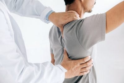 physiotherapist adjusting stroke patients back and frozen shoulder