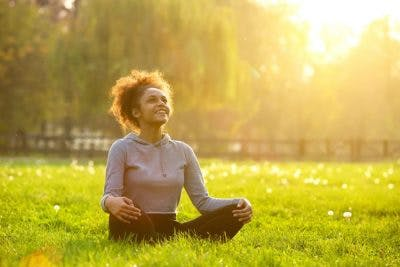 young woman sitting in grassy field cross-legged, smiling and meditating