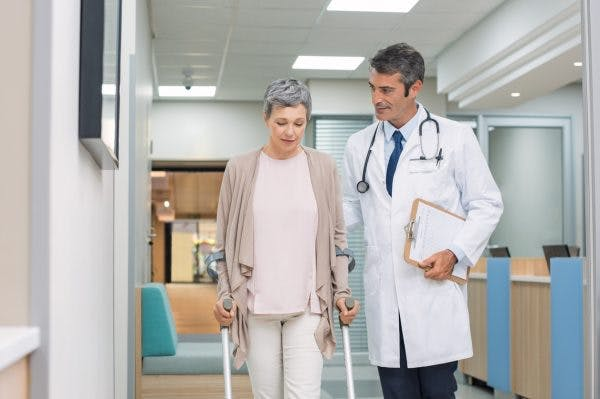 doctor escorting stroke patient out of hospital after stroke recovery plateau