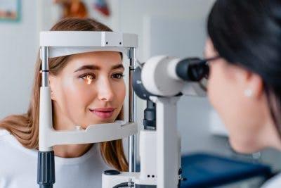 optometrist using machine to examine patient's eyes