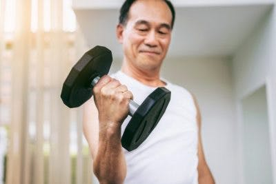 senior man doing bicep curls to reverse his muscle atrophy after stroke