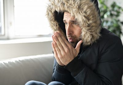 man sitting in living room wearing heavy winter coat and blowing on his hands