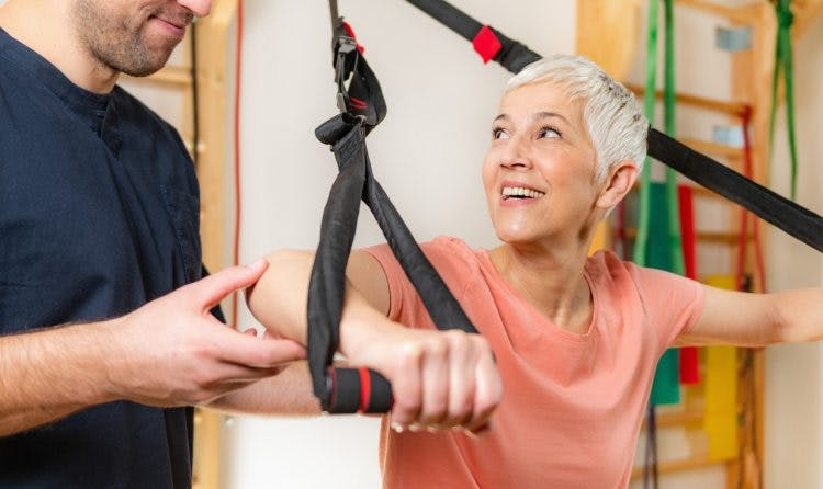 senior woman training on TRX as part of her acquired brain injury treatment