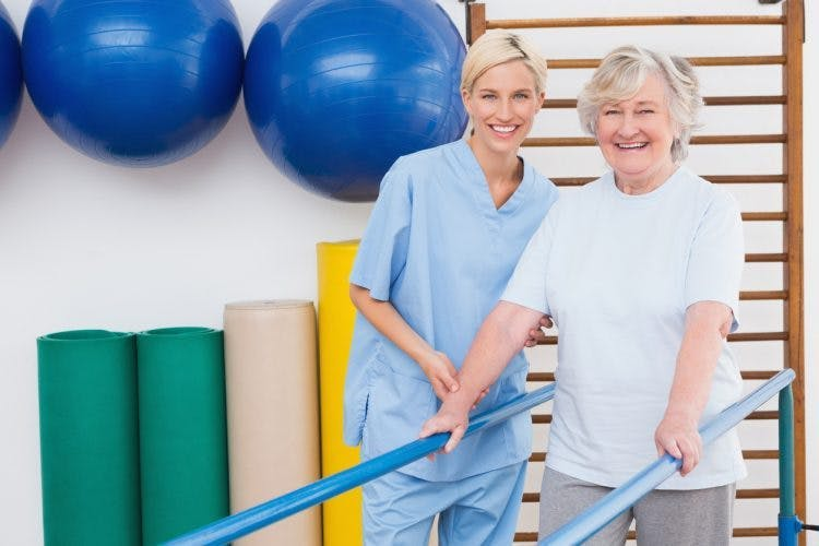 Schlaganfallpatient und Therapeut führen eine Gangrehabilitation mit Barren durch, um das Gehen nach einem Schlaganfall zu verbessern