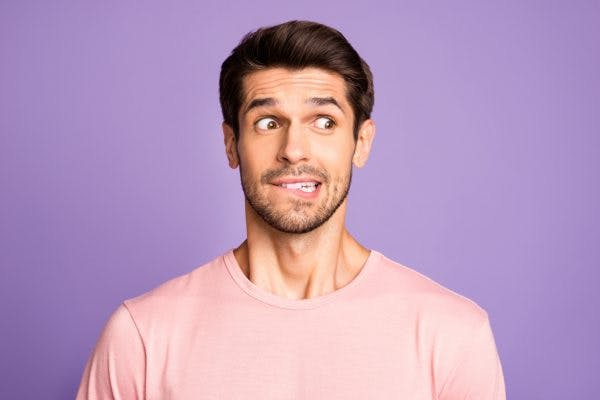 Close-up portrait of bearded guy wearing pink tshirt in front of isolated over violet purple lilac background biting lip looking nervous because he has damage to Wernicke's area