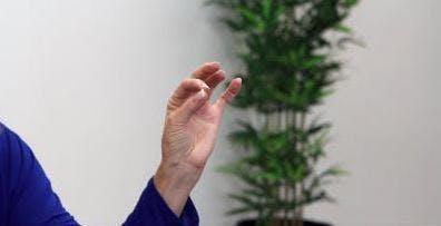Ergotherapeut berührt den Daumen, um die Fingerspitze für Handübungen zu zeigen