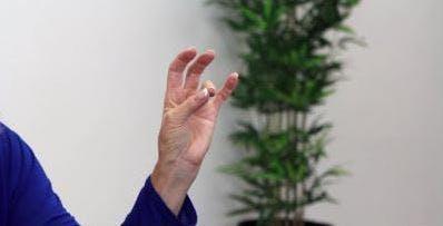 Der Therapeut berührt den Daumen, um den Finger für fortgeschrittene Handübungen zu ringen