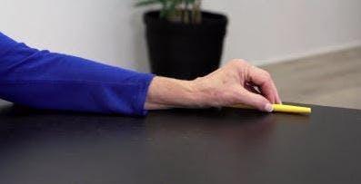 Therapeut bewegt Stift über Tisch für Handübung