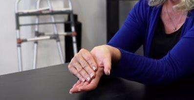 Die Therapeutin beugt ihr Handgelenk sanft nach hinten