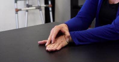 linke Handfläche nach unten auf dem Tisch mit der rechten Hand oben