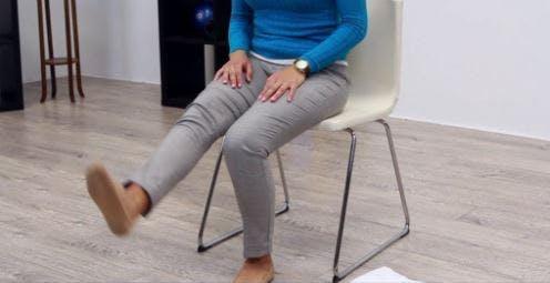 Therapeut setzt sich und streckt das rechte Bein aus