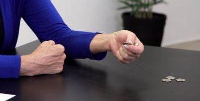 Therapeut kneift ein Viertel zwischen Daumen und Zeigefinger