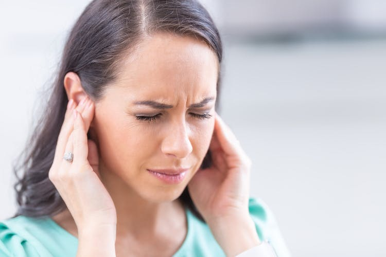 woman grimacing and rubbing her because she has tinnitus after head injury