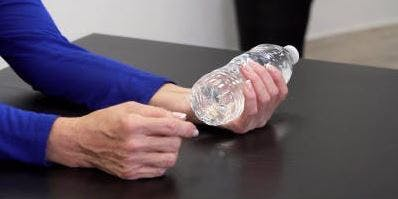 Therapeut drückt Wasserflasche in der Hand