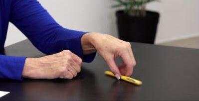 Therapeut zeigt Handübungen für Schlaganfallpatienten