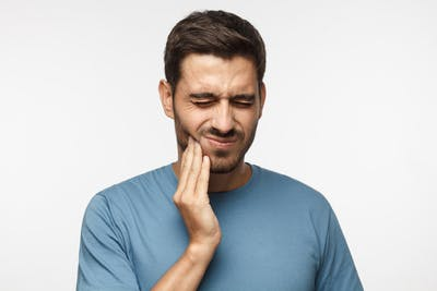 man rubbing his jaw because he has TMJ