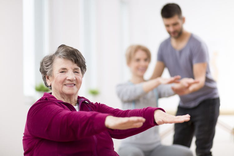 Elderly woman smiling at camera doing exercises to help with TBI recovery