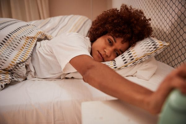 woman reaching for her alarm clock, struggling to wake up because she has post-traumatic hypersomnia