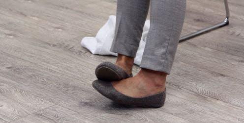 Therapeut hebt Fuß mit anderem Fuß an