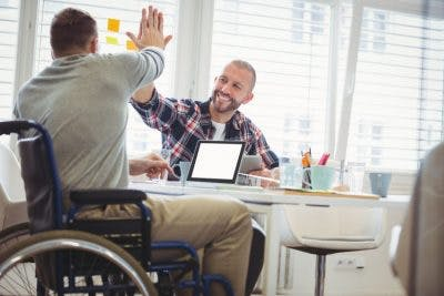 man sitting at work desk high-fiving coworker who is in a wheelchair