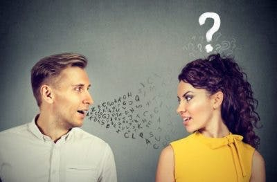 man speaking to woman but the woman has a question mark over her head to signify a language difficulty