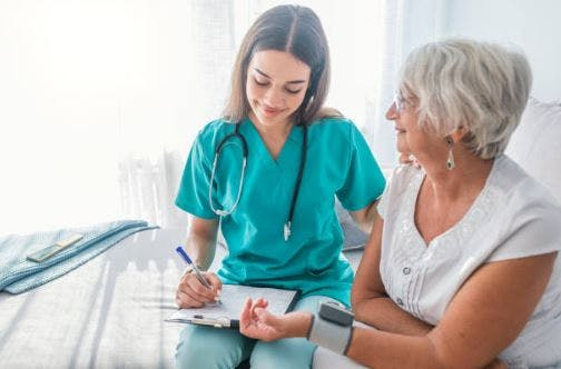 home health specialist taking blood pressure for stroke patient at home