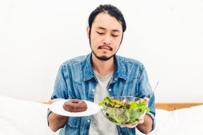 man struggling to choose between donut and salad