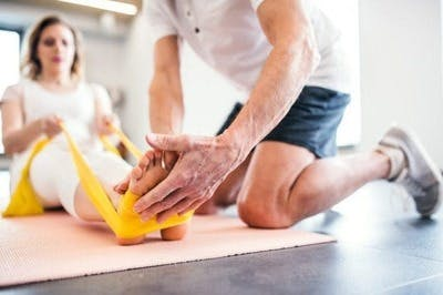therapist wrapping exercise bands around stroke patient's feet for exercise