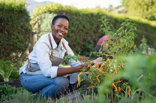 stroke patient posing with gardening tools in backyard