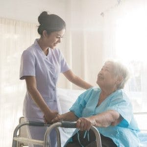 home health care workers standing next to stroke patient inside living room with hand on shoulder while stroke patient holds walker