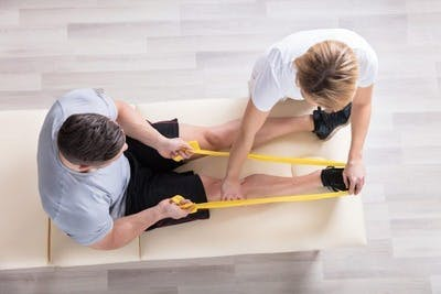 physical therapist working with stroke patient on leg exercises to help prevent falling after stroke