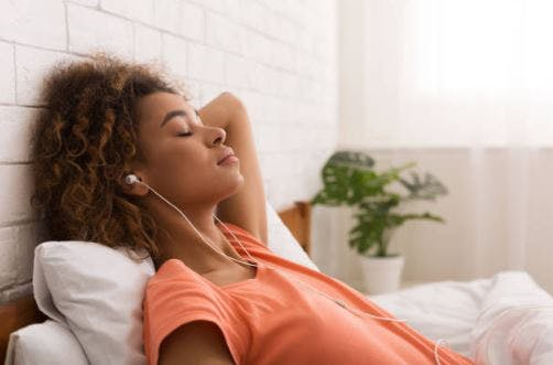 woman with headphones relaxing on bed listening to podcast