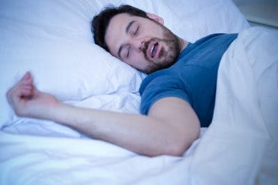 man asleep in bed snoring with mouth open