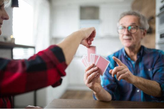 stroke patient holding playing cards while someone picks a random card from their hand