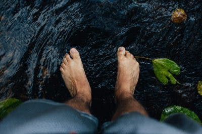 close up of man's feet standing in shallow stream