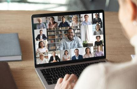woman on laptop with video chat of support group