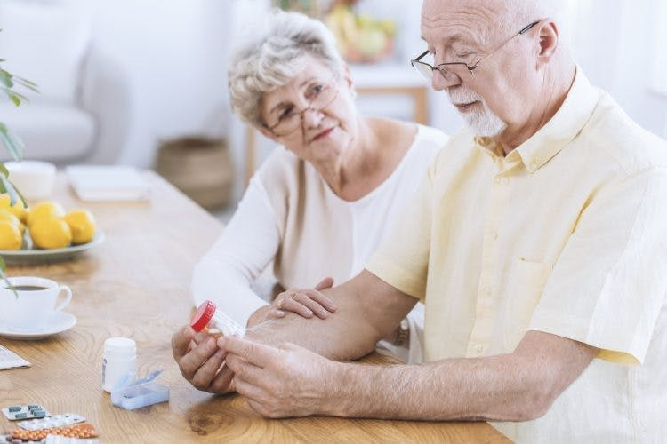 stroke patient with reading glasses on looking at medication label with his caregiver
