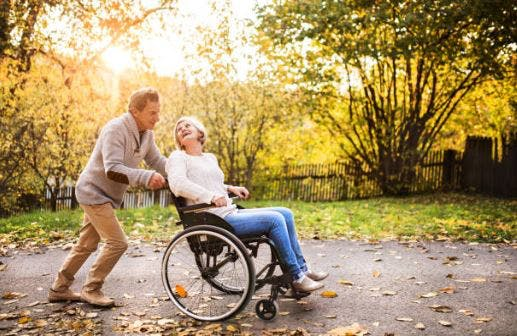 caregiver pushing stroke patient in wheelchair through path with colorful trees and falling leaves