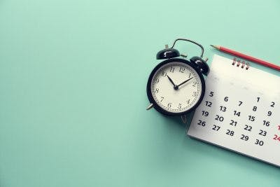 clock on mint green background next to calendar to represent the time you need to achieve long-term goals for TBI patients