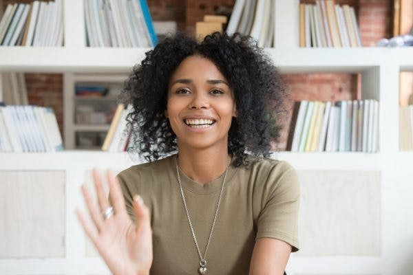 young African American woman smiling and waving