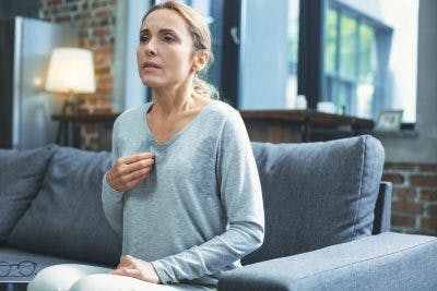 woman sweating and having a panic attack in living room