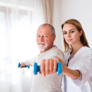 Therapist helping stroke patient lift dumbbells to overcome the effects of a stroke in the motor cortex