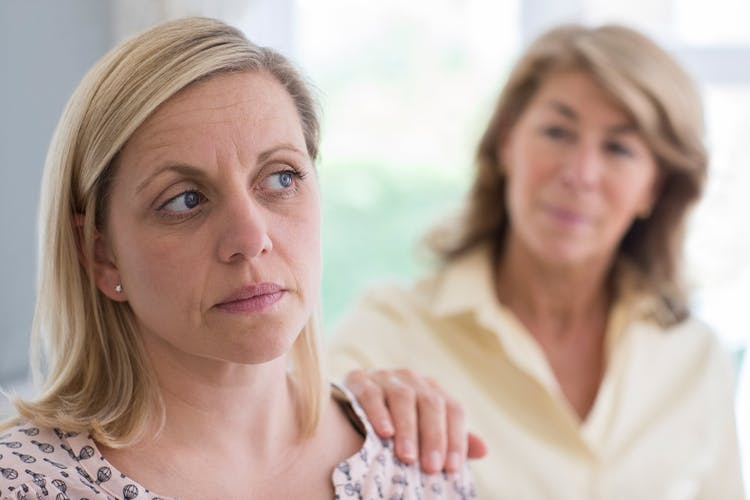 Mother putting hand on adult daughter's shoulder who has personality changes after head injury