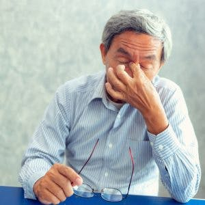 Stressed senior man rubbing bridge of nose