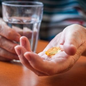 woman's hand holding fish oil tablets and glass of water