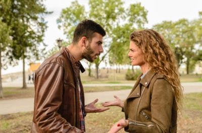 couple arguing in park because man is struggling with personality changes after head injury