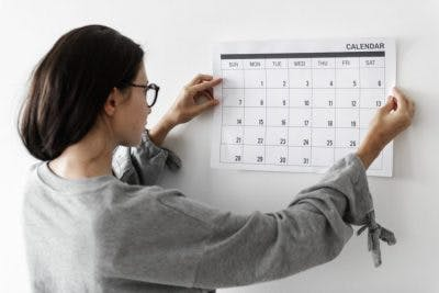 woman with glasses hanging up calendar
