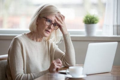 woman at computer rubbing her forehead looking confused because she has prefrontal cortex damage